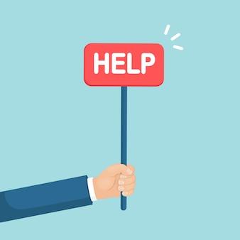 Drukke, vermoeide zakenman houdt rood bordje vast. verzoek om hulp. menselijke hand met banner. ondersteuning concept.