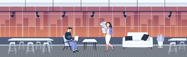 Drukke zwaarlijvige zakenman met dikke buik met behulp van laptop vrouw secretaris uitvoering mappen stapel zakenmensen deadline ongezonde levensstijl zwaarlijvigheid concept modern kantoor interieur volledige lengte