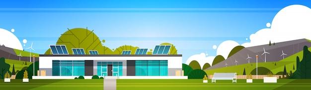 Eco-vriendelijke moderne huis met windturbines en zonnepanelen alternatieve energie concept horizontaal