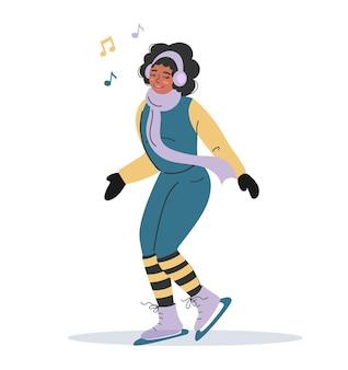 Een afrikaans-amerikaans meisje in warme winterkleren schaatst en luistert naar muziek met een koptelefoon.
