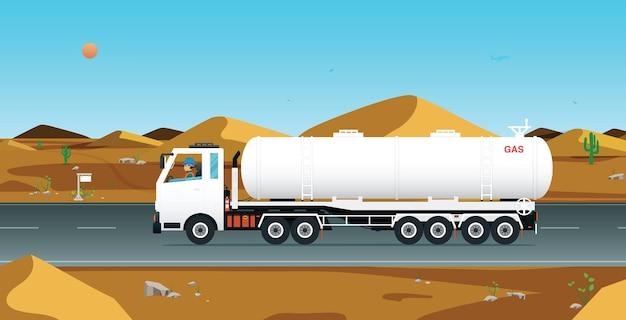 Een arbeider bestuurt een benzinevrachtwagen op een weg in een woestijngebied