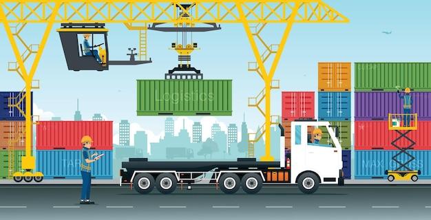 Een arbeider bestuurt een kraan om de container op de vrachtwagen te hijsen