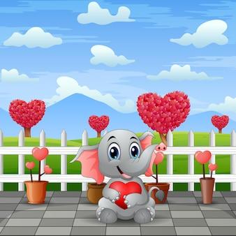 Een babyolifant die rood hart in het parklandschap houdt