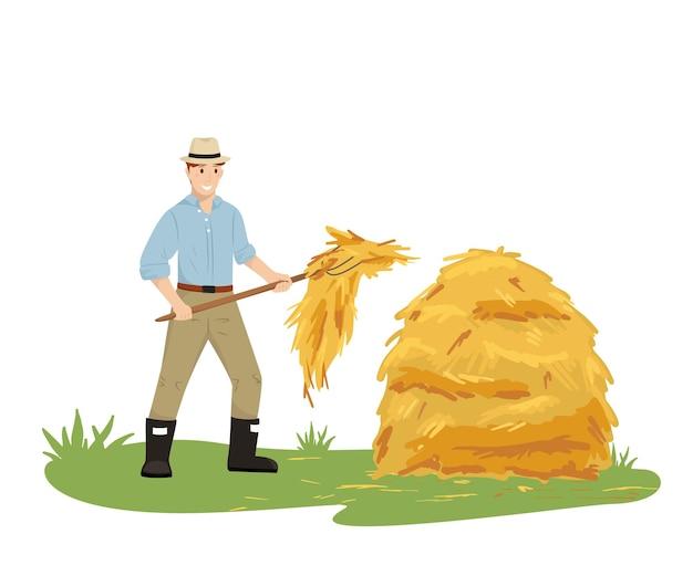 Een boer met een hoed die een hooivork vasthoudt, verzamelt hooi in een stapel landbouwwerk