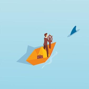 Een bussinessman in de papieren boot met haaien in zijn achterbank