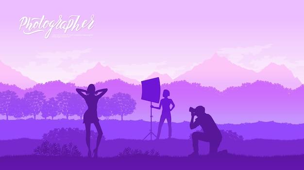 Een fotograaf met apparatuur maakt een fotosessie met modellen in natuurconcept.