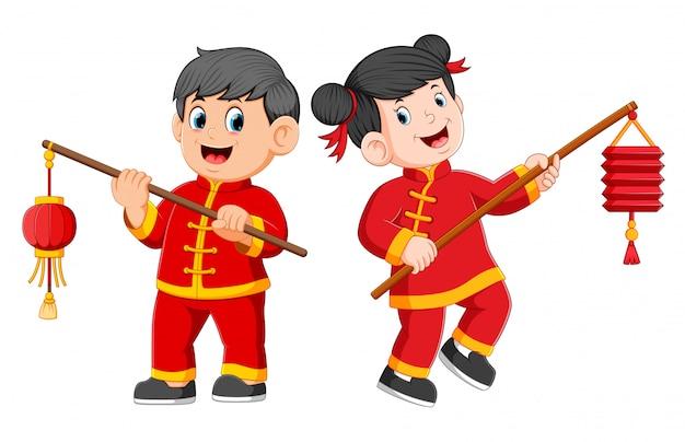 Een gelukkige kinderen staan en houden een chinese papieren lantaarn