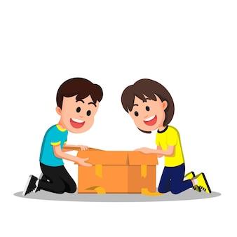 Een gelukkige kleine jongen en meisje die een kartonnen doos openen