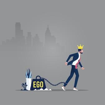 Een groot gewicht in de vorm van een ego is vastgeketend aan de voet van een man met een kroon op zijn hoofd