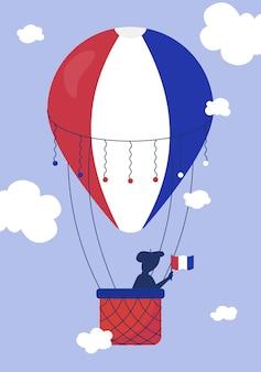 Een heteluchtballon met een silhouet van een man in een mand die de nationale vlag van frankrijk in de hand houdt