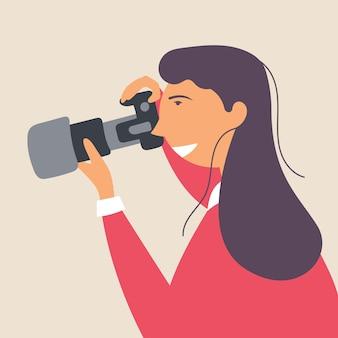 Een jong meisje fotografeert met een spiegelreflexcamera in een natuurlijke omgeving