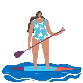 Een jong meisje in een zwempak op een rechtopstaand bord met een roeispaan in haar handen onderbord op watergolven zee v...