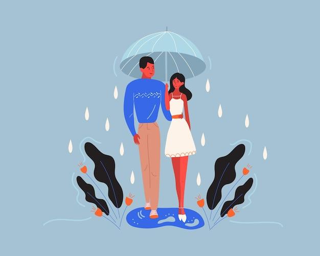 Een jong stel dat tijdens het regenen onder een paraplu loopt.