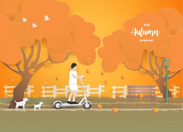 Een jonge jongen die een elektrische autoped in het park op het gras in de herfst berijdt.