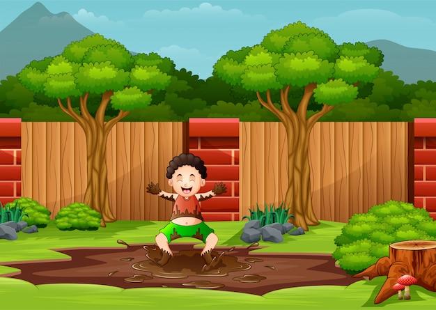 Een jonge jongen die in een modderpoel speelt