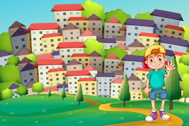Een jonge jongen die op de heuveltop tegenover het dorp staat