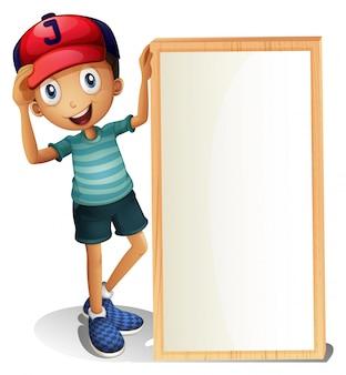 Een jonge jongen die zich naast een leeg uithangbord bevindt