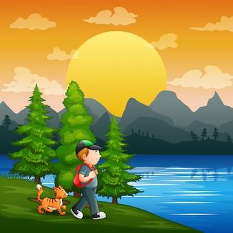 Een jonge jongen en zijn huisdier aan de rivier
