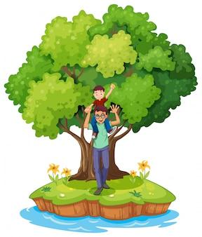 Een jonge jongen gedragen door zijn vader in de buurt van de grote boom