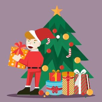 Een jonge kerstman die een geschenk houdt en naast de kerstboom staat
