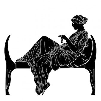 Een jonge oude griekse vrouw zit op een bed en houdt kralen in haar hand.