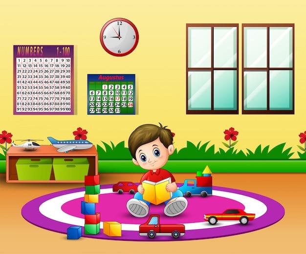 Een jongen die een boek op rond tapijt in klaslokaal leest