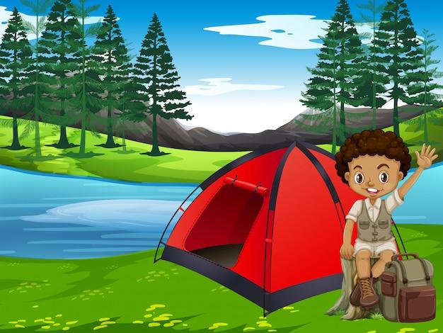 Een jongen die in bos kampeert