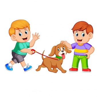 Een jongen die met zijn hond loopt