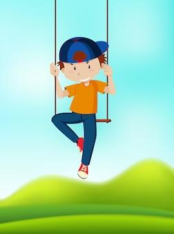 Een jongen die op schommel speelt