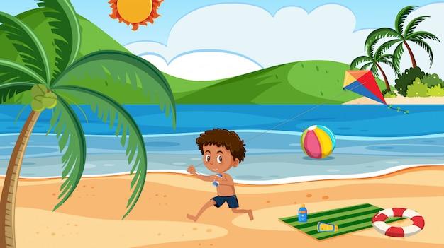 Een jongen die vlieger bij het strand speelt