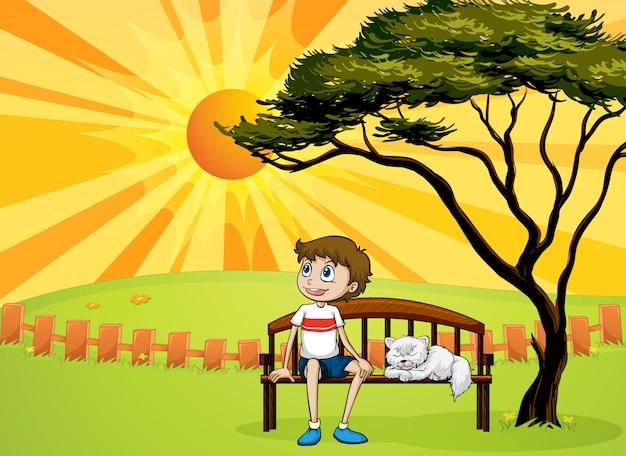Een jongen en een kat, zittend op een bankje