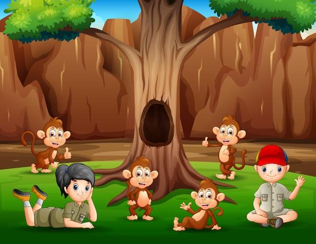 Een jongen en een meisje die onder boom met apen ontspannen