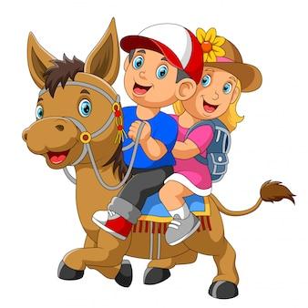 Een jongen en een meisje rijden paard