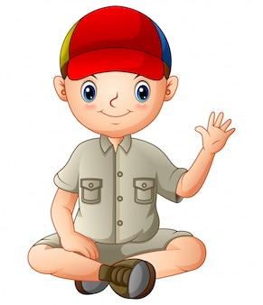 Een jongen in kampeeruitrusting zit en zwaait