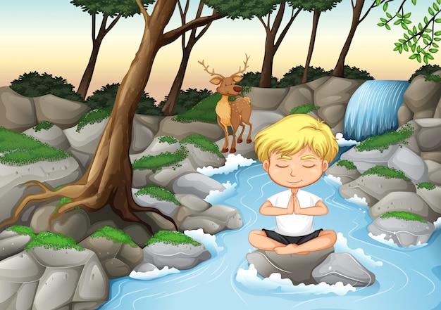Een jongen mediteert in de natuur