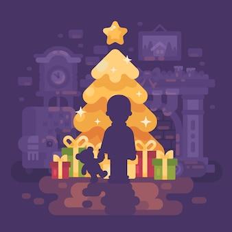 Een jongen met een teddybeer dichtbij een heldere glanzende kerstboom