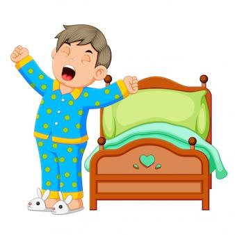 Een jongen wordt wakker en rekt zich uit in de ochtend