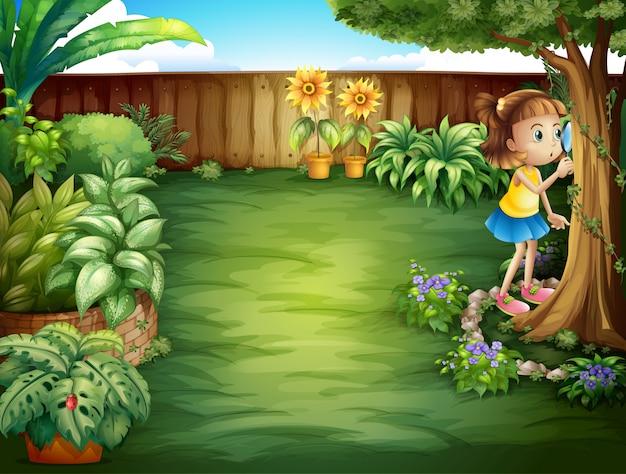 Een klein meisje dat de planten in de tuin bestudeert