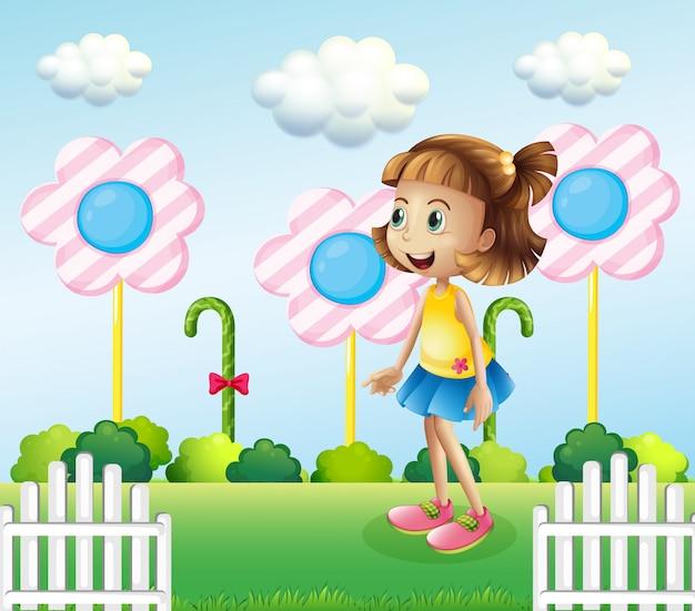 Een klein meisje in de buurt van het houten hek met gigantische snoepjes