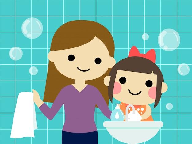 Een klein meisje wast de hand met mama