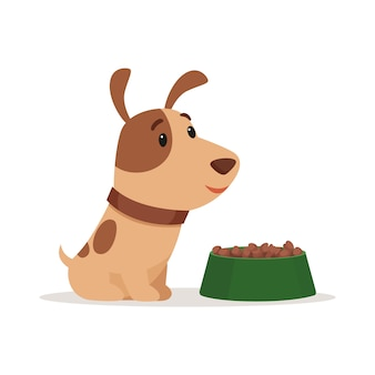 Een klein puppy lacht en zit in de buurt van een kom eten
