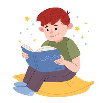 Een kleine jongen zit op een kussen en leest een boek. het kind leest graag.