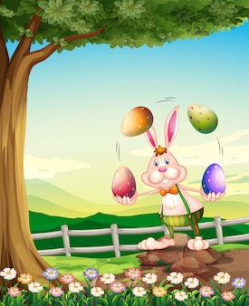 Een konijn dat met de paaseieren jongleert Premium Vector
