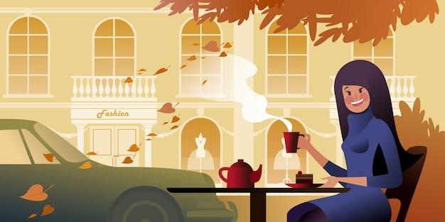 Een lachende meisje drinkt thee op het herfstterras van een stedelijk café. stad straatbeeld.