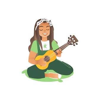 Een langharige mooie vrouw zit op het gras en speelt gitaar
