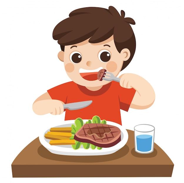 Een leuke jongen eet biefstuk met groenten voor een lunch.
