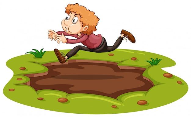 Een man die over modder springt