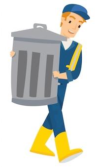 Een man draagt de vuilnisbak naar de vuilnisbelt