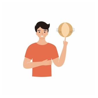 Een man houdt een bal in zijn handen. de man laat de bal rond zijn vinger draaien. leraar lichamelijke opvoeding, sportcoach.