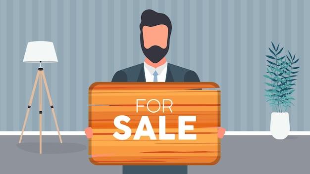 Een man met een bril houdt een houten bord vast met het opschrift te koop. jonge man met een houten bord. het concept van de verkoop van een appartement, kantoor of gebouw. vector.